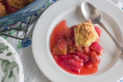 overhead image of serving of strawberry rhubarb cobbler on white plate on top of floral linens