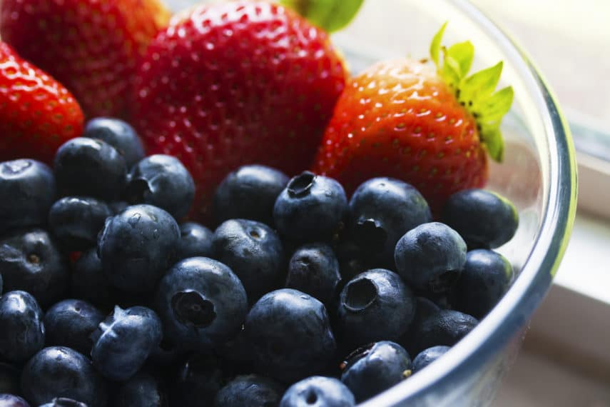 Blueberries and Strawberries in a glass bowl.