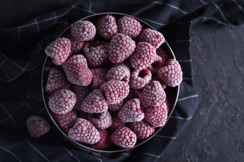 frozen raspberries in a dark bowl. Fresh vs. Frozen Fruits & Vegetables