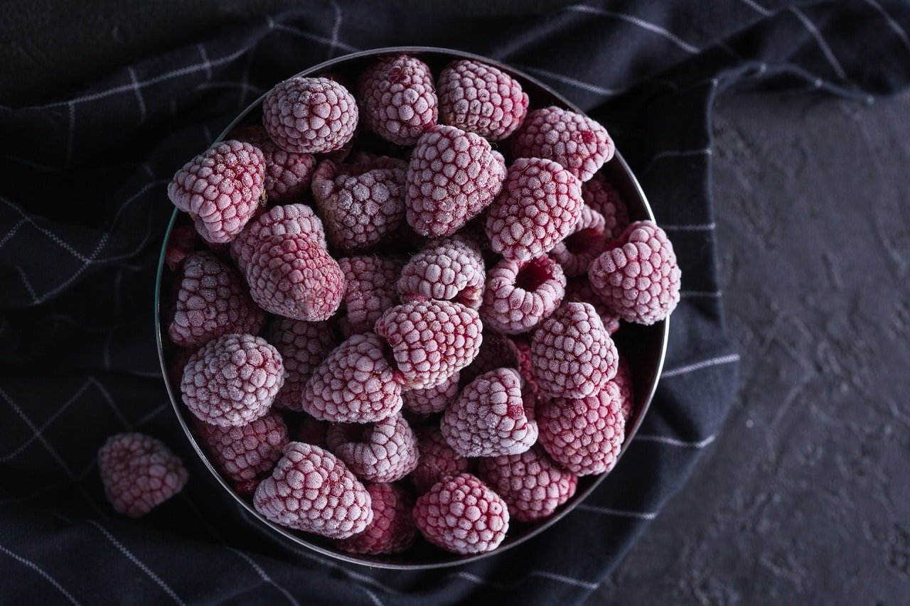 frozen raspberries in a dark bowl. Fresh vs. Frozen Fruits & Vegetables