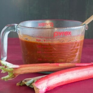 rhubarb BBQ sauce in measuring cup with fresh rhubarb alongside
