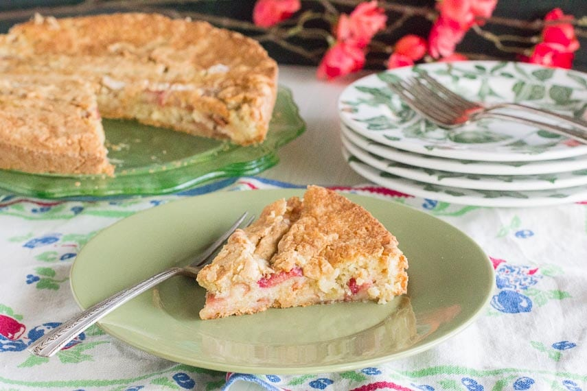 rustic rhubarb cake slice on green plate, whole cake in background on green glass plate. Floral linens and red blossoms in background