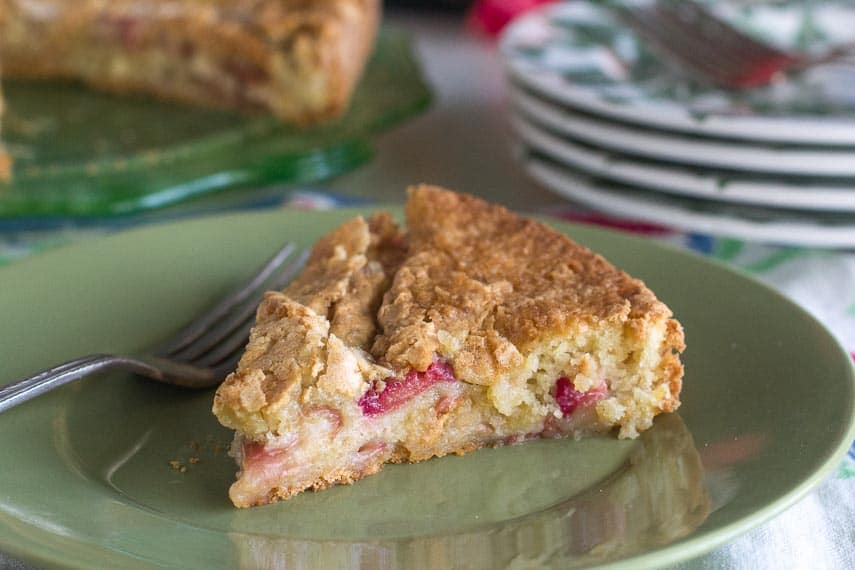 slice of rustic rhubarb cake on green plate with silver fork