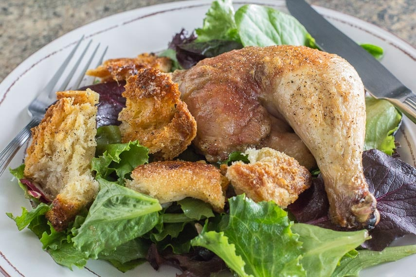 spatchcocked chicken with sourdough croutons & schmaltz on a white plate with a green salad