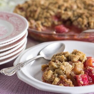 strawberry rhubarb crisp on a white plate with spoon alongside; stack of pink plates and whole crisp in background