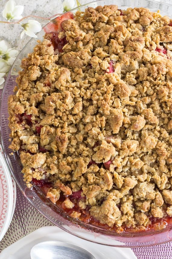 vertical image of strawberry rhubarb crisp in a clear glass pie plate