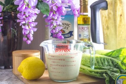Caesar salad dressing in measuring cup with ingredients in background