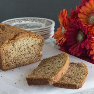 FODMAP IT banana bread closeup on white cutting board with Gerbera daisies in background