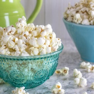 Garlicky Parmesan Herb Popcorn in clear teal glass bowl on gray quartz counter