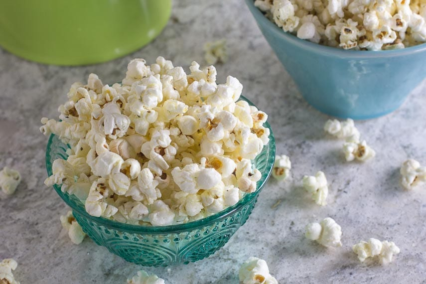 Garlicky Parmesan Herb Popcorn in teal glass bowl on gray quartz counter