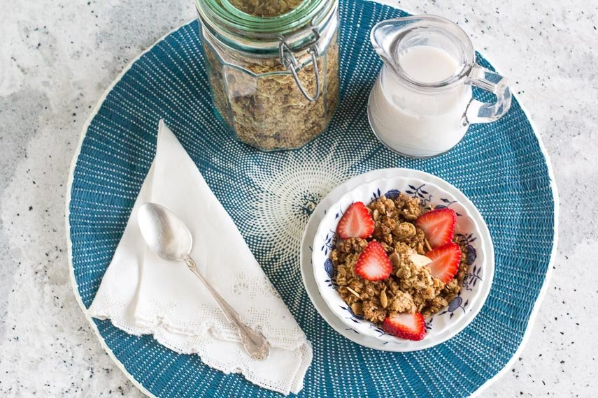 Gingersnap granola in a blue and white bowl on a blue placemat with a pitcher of milk