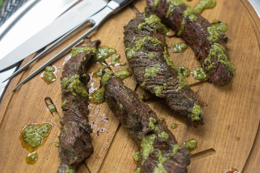 Grilled Hanger Steak with Charmoula Sauce on a cutting board with carving knife and fork