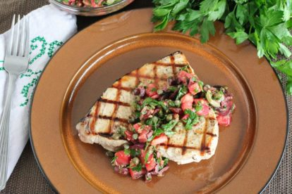 Grilled Swordfish with Tomato Olive Salsa on a brown plate