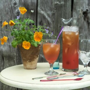 Strawberry Arnold Palmer in glass pitcher and glass against barn board