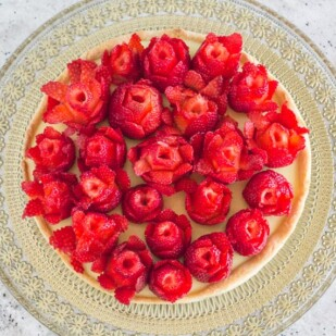 Strawberry rose tart with pastry cream and tart crust on gold glass platter