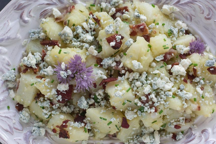 closeup image of Potato Salad with Bacon, Chives & Blue Cheese in decorative white bowl