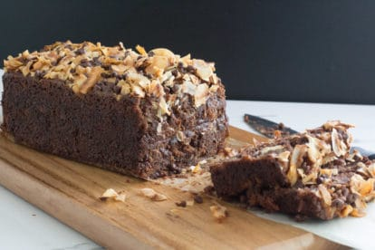 chocolate coconut banana bread on a wooden cutting board, with slices and knife alongside