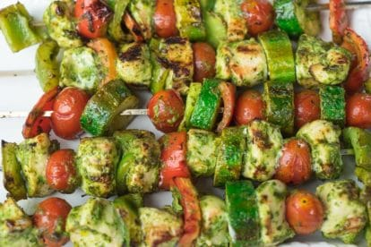 closeup of grilled chicken and vegetable kebobs on a white platter