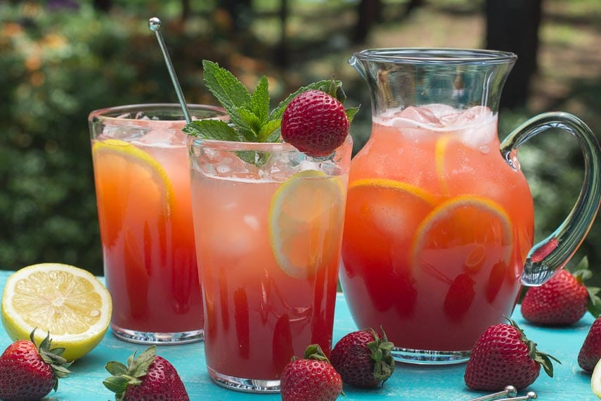 closeup of strawberry lemonade in clear glasses and pitcher, with sprig of mint