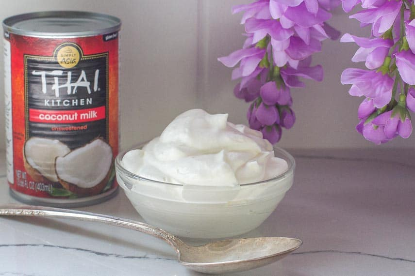 coconut whipped cream in gladd bowl with spoon and can of coconut milk