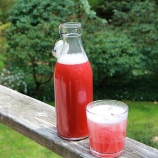 glass and bottle of rhubarb ginger syrup on railing of deck