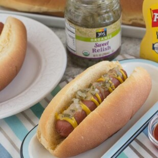 overhead image on two hot dogs on a white plate, with condiments