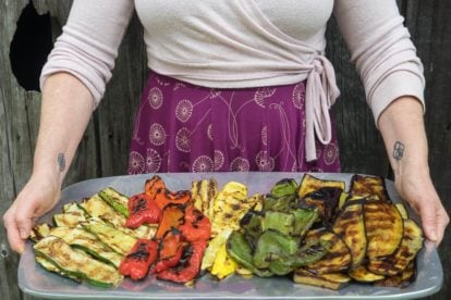 low FODMAP Grilled vegetables on a large platter, held by a woman in a dress