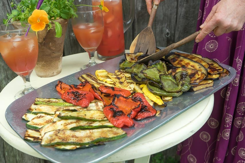 low FODMAP grilled vegetables on a platter with a woman servings them with wooden servers; iced tea in background