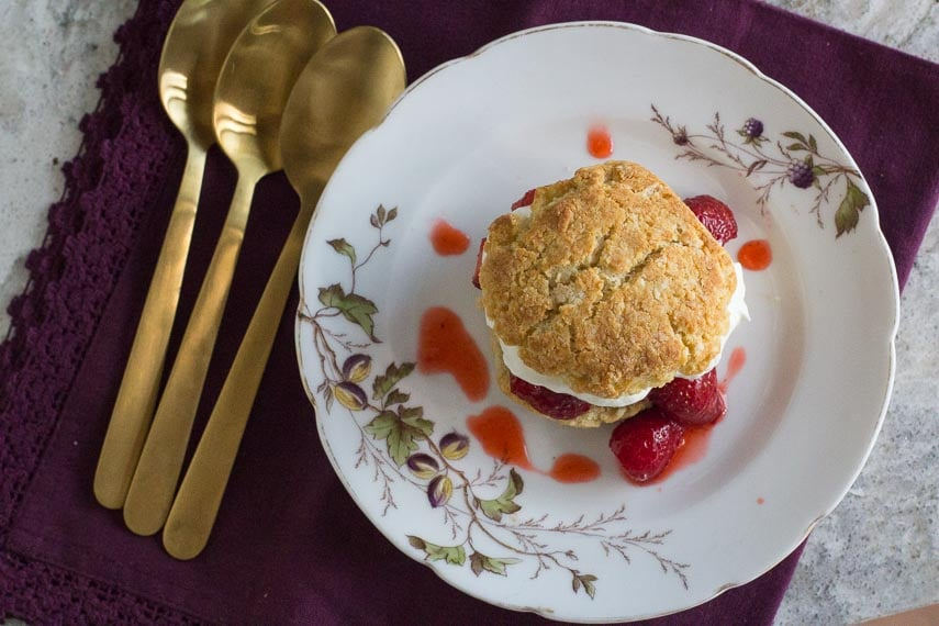 overhead image of strawberry shortcake on a white floral plate with gold spoons alongside