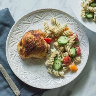 Fusilli Pasta Salad with Chickpeas & Feta on white plate with roast chicken thigh