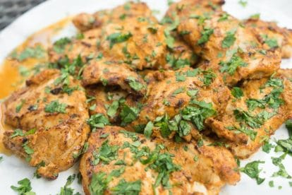 platter of spiced yogurt grilled chicken garnished with cilantro