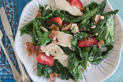 Spinach Salad with Hot Bacon Dressing, Chicken, Blue Cheese & Strawberries on a white plate with blue background