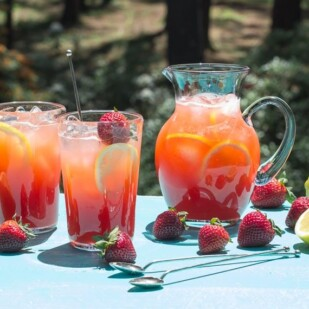 strawberry lemonade in pitcher and glasses on an aqua wooden board out on the deck in full sun