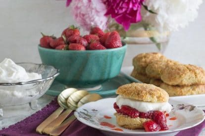 strawberry shortcake on a white plate with gold spoons alongside; berries and peonies in background