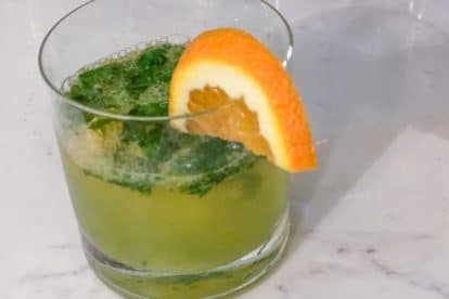 Basil orange smash in a short glass with orange wedge