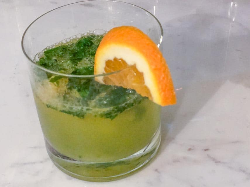 Basil orange smash in a short glass with orange wedge