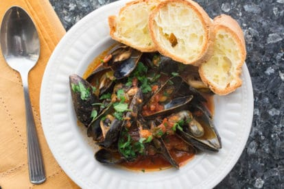 Mussels with Tomatoes & White Wine with Garlic Toasts in a white bowl