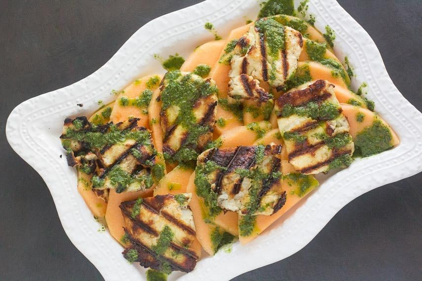 overhead image of grilled halloumi salad with melon on rectangular white platter