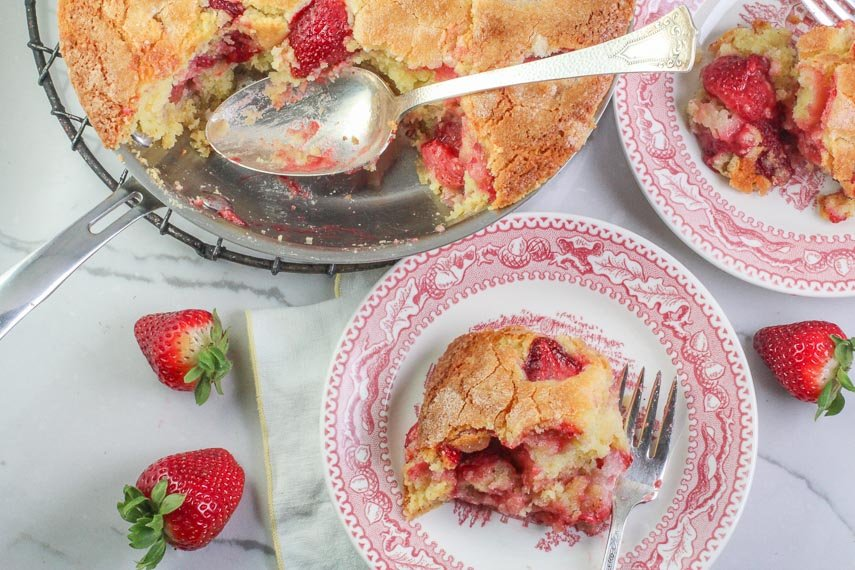 overhead image of strawberry yogurt skillet cake on pink plate and in skillet with serving spoon
