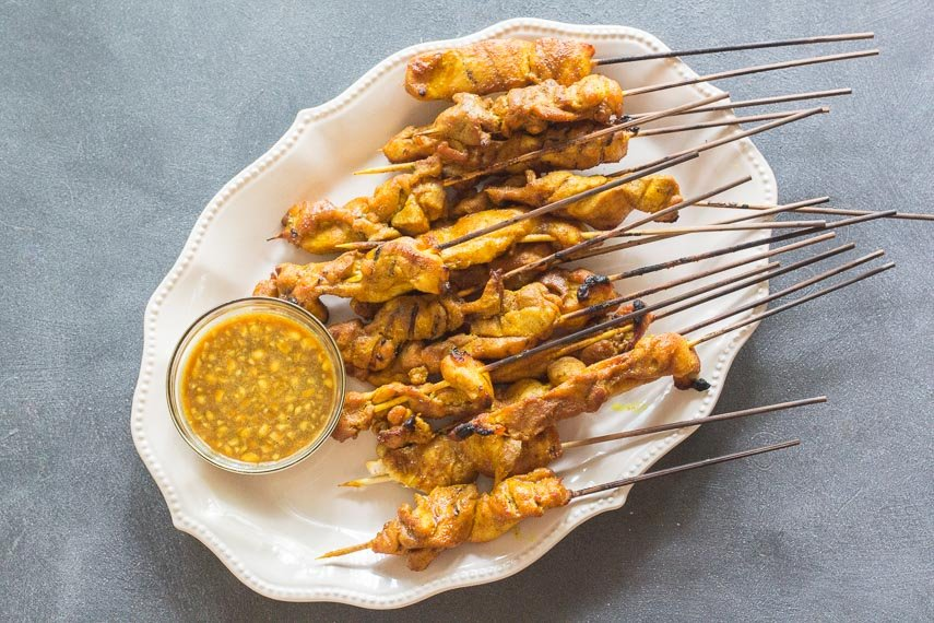 Singapore chicken satay on oval white platter with dipping sauce
