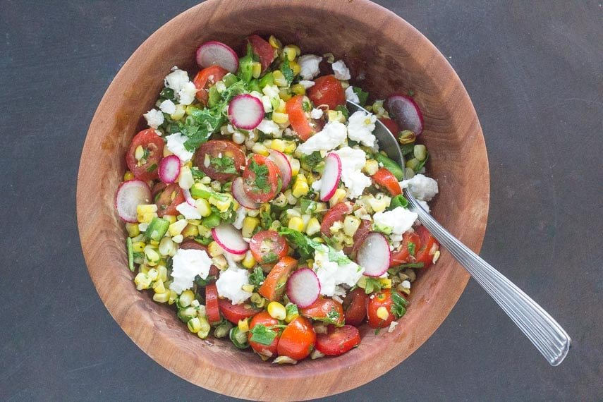 Grilled corn salad with feta in a wooden bowl on dark background