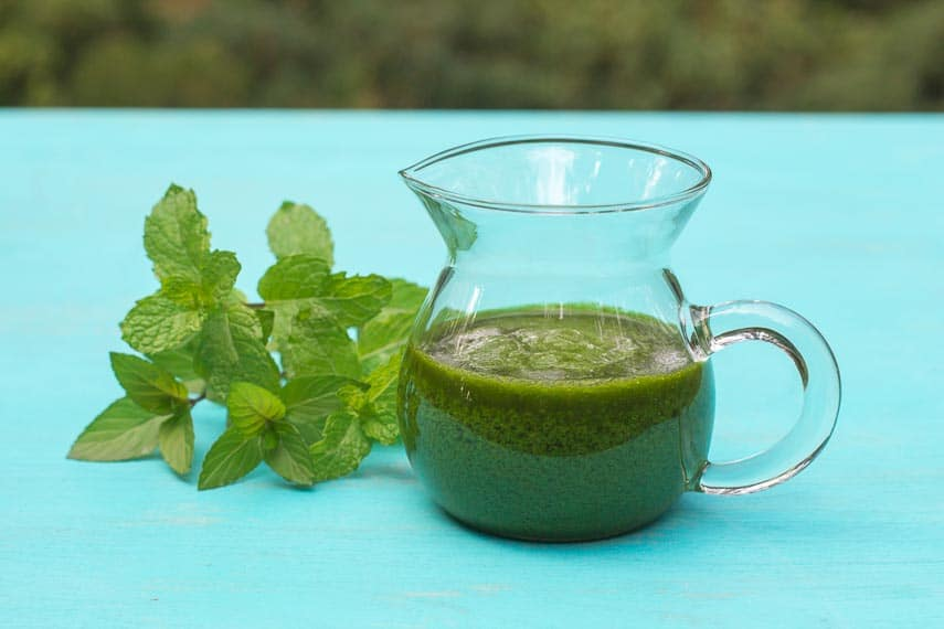 Low FODMAP Mint salsa verde in glass pitcher with fresh mint alongside