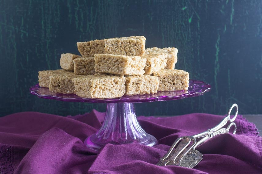 cappuccino rice crispy treats on purple pedestal with silver serving implement alongside