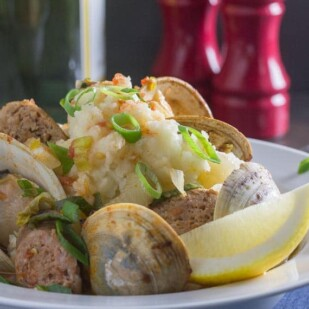 closeup of roast clams and spicy sausages with mashed potatoes in white bowl