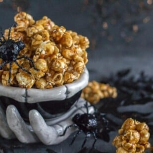 closeup of gingerbread caramel crunch popcorn in creepy ceramic skeleton bowl with black spiders