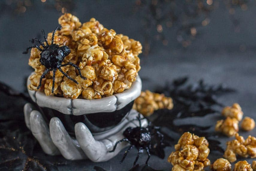 closeup of low FODMAP gingerbread caramel crunch popcorn in creepy ceramic skeleton bowl with black spiders