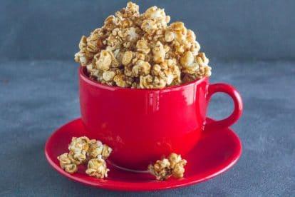 gingerbread caramel crunch popcorn in red ceramic mug on saucer
