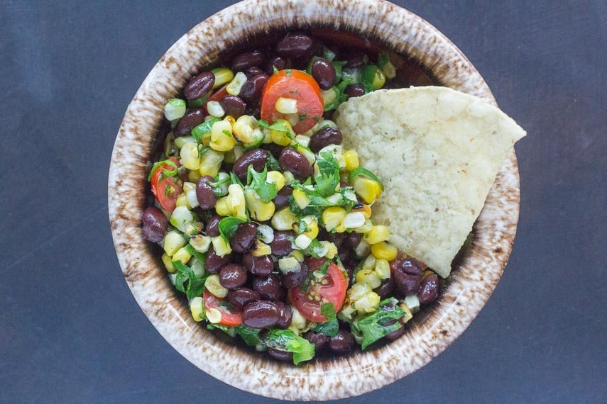 grilled corn salsa with black beans in a small bowl and a corn chip for dipping