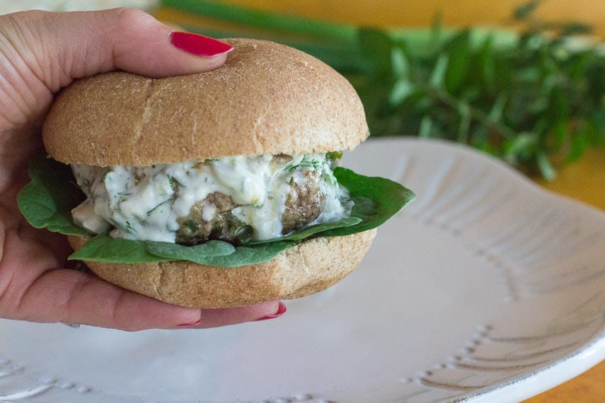 lamb burgers with tzatziki sauce, held in hand over a white plate