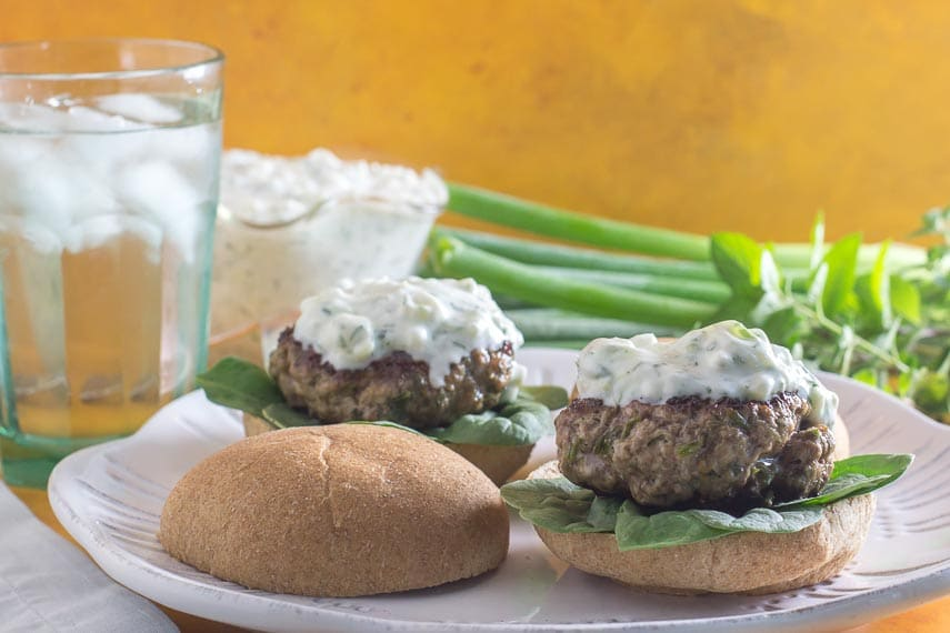 lamb burgers with tzatziki sauce on open rolls